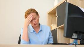 Een vrouw die aan pijn in haar hoofd lijden terwijl het werken aan een computer 4k, langzame motie stock videobeelden