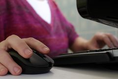 Een vrouw die bij een computer werken Hand op de muis royalty-vrije stock fotografie