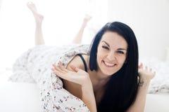 Een vrouw die bij het bed en het glimlachen liggen - sexy provocatief stock afbeeldingen