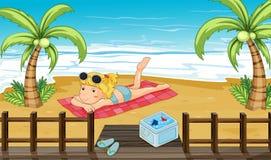 Een vrouw die bij het strand zonnebaden Stock Afbeelding