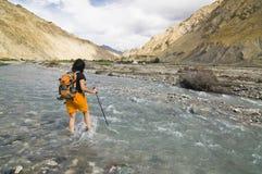Een vrouw die de Markha Rivier, Ladakh, India kruist stock foto's