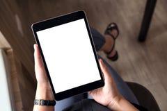 Een vrouw die dwars legged en het houden zwarte tabletpc met het lege witte Desktopscherm zitten in bureau royalty-vrije stock afbeelding
