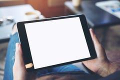 Een vrouw die dwars legged en het houden zwarte tabletpc met het lege witte scherm op dij in koffie zitten Stock Afbeeldingen