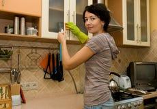 Een vrouw die een keuken schoonmaakt Stock Foto's
