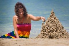 Een vrouw die een zandkasteel bouwt Stock Foto