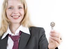 Een vrouw die een zilveren sleutel houdt Royalty-vrije Stock Fotografie