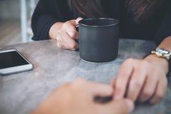 Een vrouw die en elkaar raken houden overhandigt met het voelen van liefde met koffiekop en mobiele telefoon op lijst in koffie stock foto