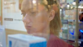 Een vrouw die een glasvitrine bekijken in de opslag 4k, achtergrondonduidelijk beeld stock video