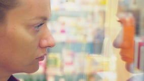 Een vrouw die een glasvitrine bekijken in de opslag 4k, achtergrondonduidelijk beeld stock footage