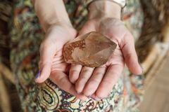 Een vrouw die een groot, lichtgevend kwartskristal houden lijkt krachtig stock foto's