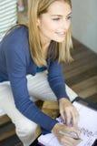 Een vrouw die in haar agenda schrijft Royalty-vrije Stock Afbeeldingen