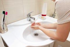 Een vrouw die handen met water in badkamersgootsteen wensen Van de Deseasepreventie en hygiëne concept Nuttige, goede gewoonte royalty-vrije stock afbeeldingen