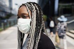 Een vrouw die hygiënisch masker in openlucht dragen stock fotografie