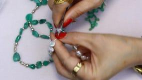 Een vrouw die juwelen met Columbiaanse smaragden maken stock footage