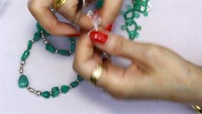 Een vrouw die juwelen met Columbiaanse smaragden maken stock video