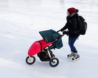 Een vrouw die met haar kinderwagen op een openluchtpiste in Montreal schaatsen stock foto's