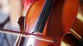Een vrouw die met rood haar de cello met een boog spelen stock video