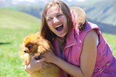 Een vrouw die met een weinig rode hond spelen stock foto