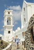 Een vrouw die naar de kerk in Fira, Santorini, Griekse Eilanden lopen stock fotografie