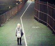 Een vrouw die onderaan de weg lopen Stock Foto's