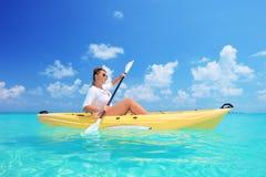 Een vrouw die op een zonnige dag kayaking Stock Afbeeldingen