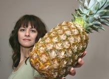 Een vrouw die pijnboomappel aanbiedt Stock Afbeeldingen