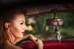 Een vrouw die retro auto op een achtergrond van bos drijven Royalty-vrije Stock Afbeeldingen