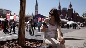 Een vrouw die een smartphone gebruiken spreekt op Rood Vierkant in Moskou, voor het Kremlin stock videobeelden