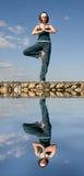 Een vrouw die yoga op een steen doet hierboven - water Royalty-vrije Stock Foto