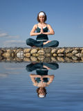 Een vrouw die yoga op een steen doet hierboven - water royalty-vrije stock afbeelding