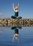 Een vrouw die yoga op een steen doet hierboven - water stock afbeeldingen