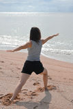 Een vrouw die yogaoefeningen op een kust doet Stock Foto's