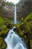 Een vrouw die zich op de rots bij Mooie dalingen van bos, Westkust de V.S. bevinden Watson Falls is waterval op Watson Creek stock afbeeldingen