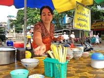 Een vrouw dient een noedelsoep in een noedelwinkel in Mandalay, Myanmar Stock Fotografie