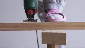 Een vrouw doet een niet vrouwelijk werk - zagend een houten raad met een elektrische figuurzaag stock video