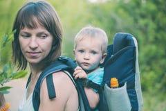 Een vrouw draagt een rugzak met haar baby Royalty-vrije Stock Foto's