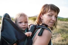 Een vrouw draagt een rugzak met haar baby Stock Afbeeldingen