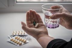 Een vrouw drinkt haar pillen stock afbeeldingen