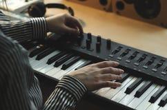 Een vrouw in een gestreept overhemd speelt de synthesizer en stemt het royalty-vrije stock foto