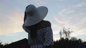 Een vrouw in een hoed in een winderig weer stock footage