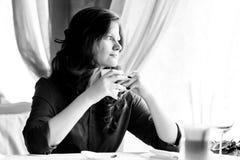 Een vrouw in een restaurant drinkt koffie Stock Fotografie