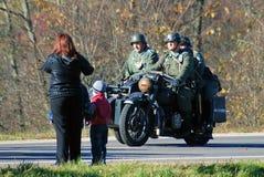 Een vrouw en de kinderen bekijken drie militaire mannen in retro eenvormig Stock Foto's