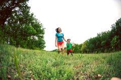 Een vrouw en haar zoon lopen langs het gras Stock Foto's