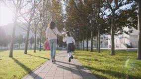 Een vrouw en klein meisje op school die in het park, steadicam, achteraanzicht loopt stock video