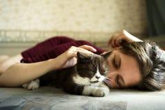 Een vrouw en een klein zwart-wit Brits katje liggen op de bank stock fotografie
