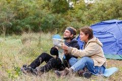 Een vrouw en een man in het hout bekijken de kaart dichtbij de tent Stock Fotografie