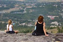 Een Vrouw en een meisje zitten op de rand van een klip en onderzoeken de afstand royalty-vrije stock afbeelding