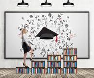 Een vrouw in formele kleding gaat op het boekenrek uit Een concept verschillend niveau van onderwijs Een geschetste graduatiehoed Royalty-vrije Stock Afbeeldingen
