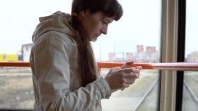 Een vrouw gaat door tram en en gebruikt slimme telefoon stock footage