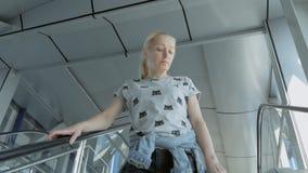 Een vrouw gaat onderaan de roltrap in een bedrijfscentrum of een luchthaven stock video